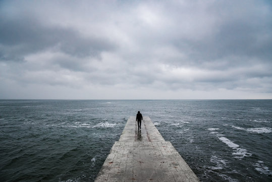 Back view portrait of young man goes to sea on pier