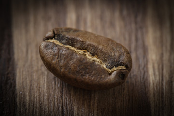 One roasted cofee bean isolated on wooden background