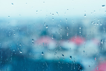 background image of a rain texture on a window pane. Textured background of a window viewing on the street in drops of pouring rain. The phenomenon of nature is rain. Wallpaper texture of water drops
