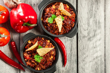 Bowls of hot chili con carne with ground beef, beans, tomatoes a