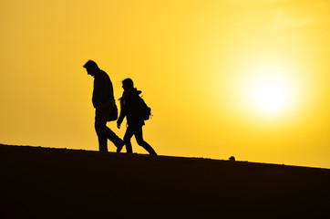 Silhouette of a Man and a Woman Walking on the Sand Dunes of the Sahara Desert During Sunrise