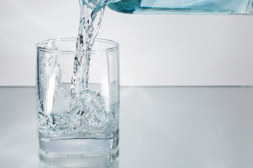 Decanter filling in glass of water splash