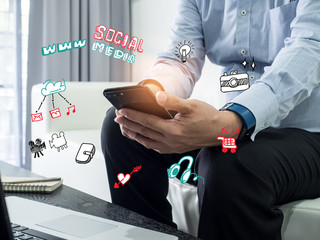 Close up of a man using mobile smart phone.Businessman working from home using smart phone and notebook computer, man's hands using smart phone , man at his workplace using technology, flare light