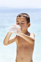 Thirsty child drinking water at the beach.