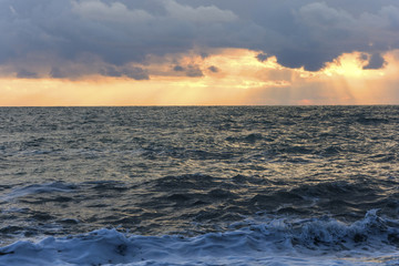 Waves of the black sea illuminated by the setting sun