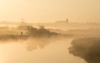 Foto auf Leinwand Fluss Man walking along banks of river on misty morning