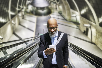 Businessman with smartphone reading messages on escalator