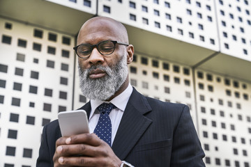 Mature businessman reading smartphone messages