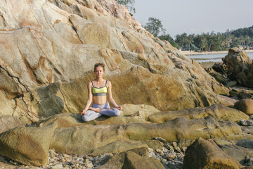Woman sitting in lotus seat, meditating on the beach
