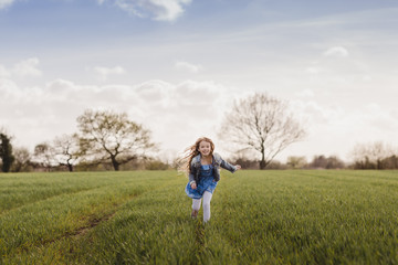 Smiling girl running on a field