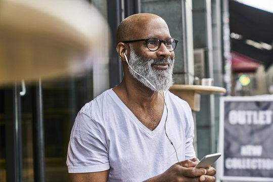 Mature man using smartphone in coffee shop