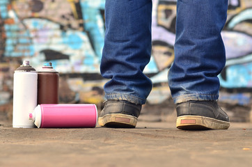 A photography of a certain number of paint cans against the graffiti background