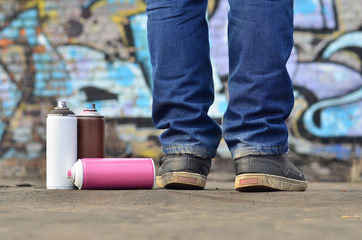 A still-life of several used paint cans of different colors against the graffiti wall