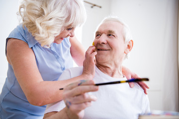 portrait of happy senior man and woman in art workshop
