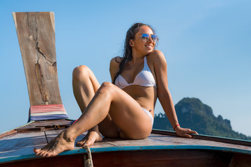Young smiling caucasian woman in bikini resting on a boat on a sunny day