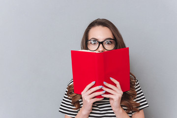 Surprised young lady standing over grey wall holding book