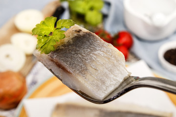 marinated herring with parsley on a fork