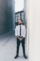 Young handsome caucasian bearded businessman posing outdoor
