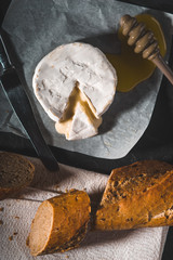 Brie cheese  with honey and bread on the stone background top view