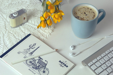 Desktop. Creative process. Morning in the office. Holiday at work. Coffee on the table. Yellow flowers. Keyboard. Crocuses.