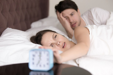 Young sleepy man and woman trying to turn off annoying loud waking up signal of alarm clock, lying in bed in the morning, feeling bad after sleepless night, having a headache or hangover