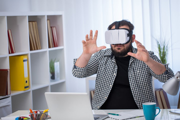 Future is now. Handsome young man in VR headset while sitting in creative office