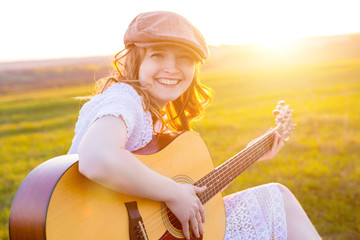 Blonde girl sitting on green grass meadow and playing on guitar