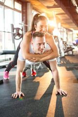 Young sporty couple working out together in gym. Man is doing plank exercise while girl is lying on him.