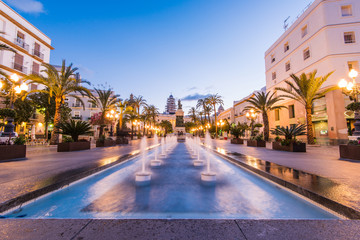 Illuminated square in Cadiz with fountains at twilight