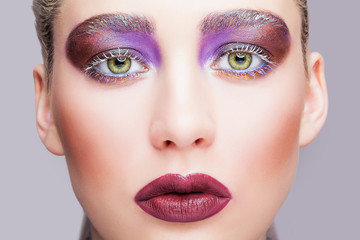 Female green pistachio colour eye with evening violet eyes shadows, white eyelashes and purple lips makeup