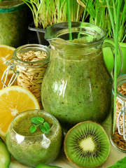 Green smoothie made of spinach, kiwi, cucumber, lemon and mint with seeds in different glass vessels for healthy nutrition