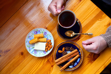 The man at the tasty breakfast. Coffee-making with sweets. Male hands holding a cup of coffee, top view