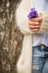 Woman holding beautiful snowdrop.  first spring flowers in a forest.  Wild flowers. spring concept.