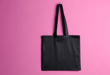 Textile bag on color background