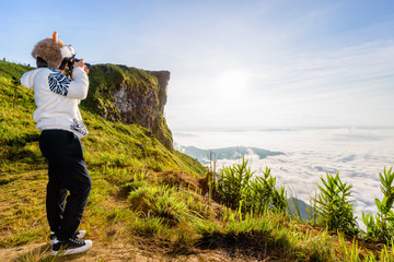 Asian hiker woman with digital camera photographing beautiful natural landscape of sky clouds and fog during sunrise in winter on mountain at Phu Chi Fa Forest Park, Chiang Rai Province, Thailand