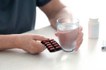 Elderly woman with pills and glass of water at home, closeup