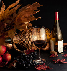 vintage scenery: glass of ruby red wine with grapes, red apples, autumn leaves and old bottle of wine