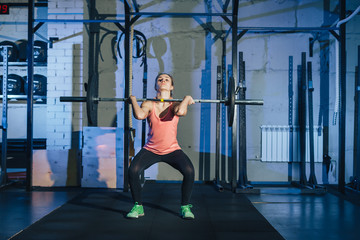 Muscular young fitness woman lifting a weight crossfit in the gym. Fitness woman deadlift barbell. Crossfit woman. Crossfit style.