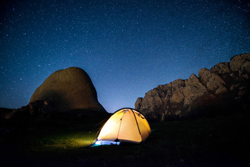 Glowing camping tent in the mountains under a starry sky