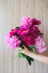 white caucasian girl holding red and pink peonies bouquet at wood wall backdrop