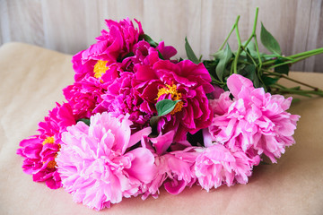 bouquet of pink and red cut peonies on kraft paper background