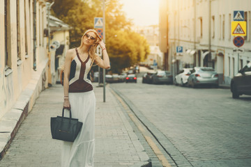 Attractive adult tall caucasian woman in long white skirt, sunglasses and with bag is fixing her hair while standing on street during sunny summer day with copy space for your advertising message