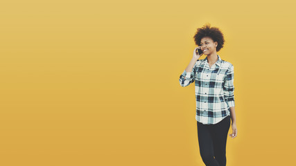 Beautiful Brazilian black girl is talking by phone with friend while standing in front of cleared separated yellow background with copy space for your advertising text message or promotional content