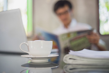 A white cup of coffee on the foreground with elegant young businessman reading newspaper at office blur background.