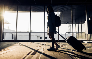 Silhouette of young girl walking with luggage walking at airport terminal window at sunrise time,travel concept,journey lifestyle