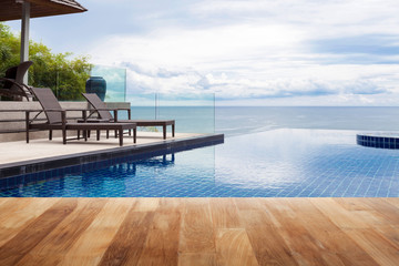 Wood table top on Beach chair in outdoor with swimming pool and sea view andaman sea.