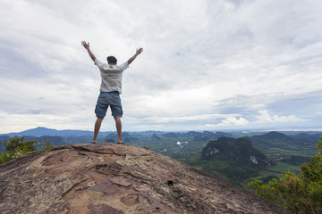 Traveler man standing on big stone holding his hand up and see landscape view at Dragon Crest mountain, popular landmark travel adventure in krabi thailand.