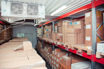 Rows of shelves with boxes and other goods in modern warehouse