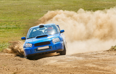 A blue rally car rides along a dusty road