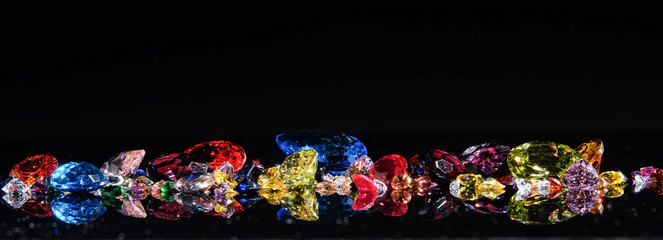 Colorful of different gemstones with space for text on black background.